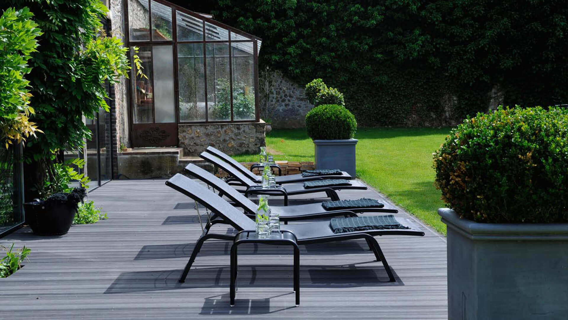 Chateau Perche loungers on a dark wooden patio with greenhouse in the back
