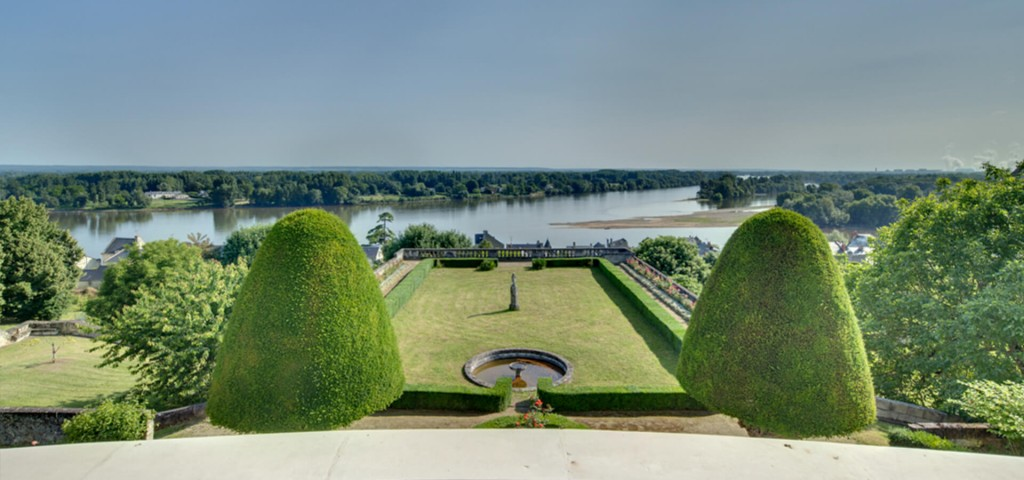 Chateau in Loire shape cut trees and courtyard with view over lake