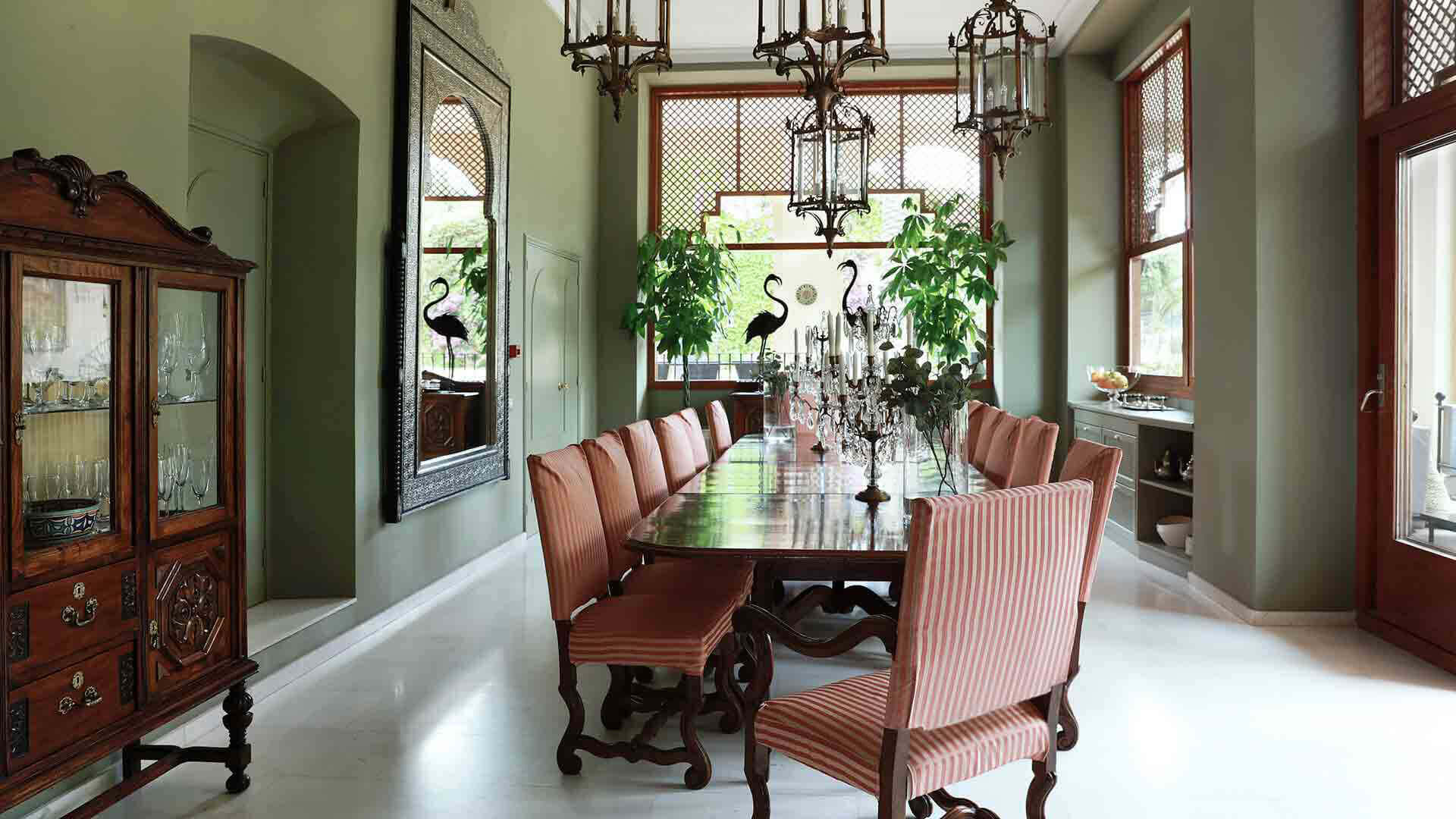 Large property outside Barcelona green dining room with red chairs