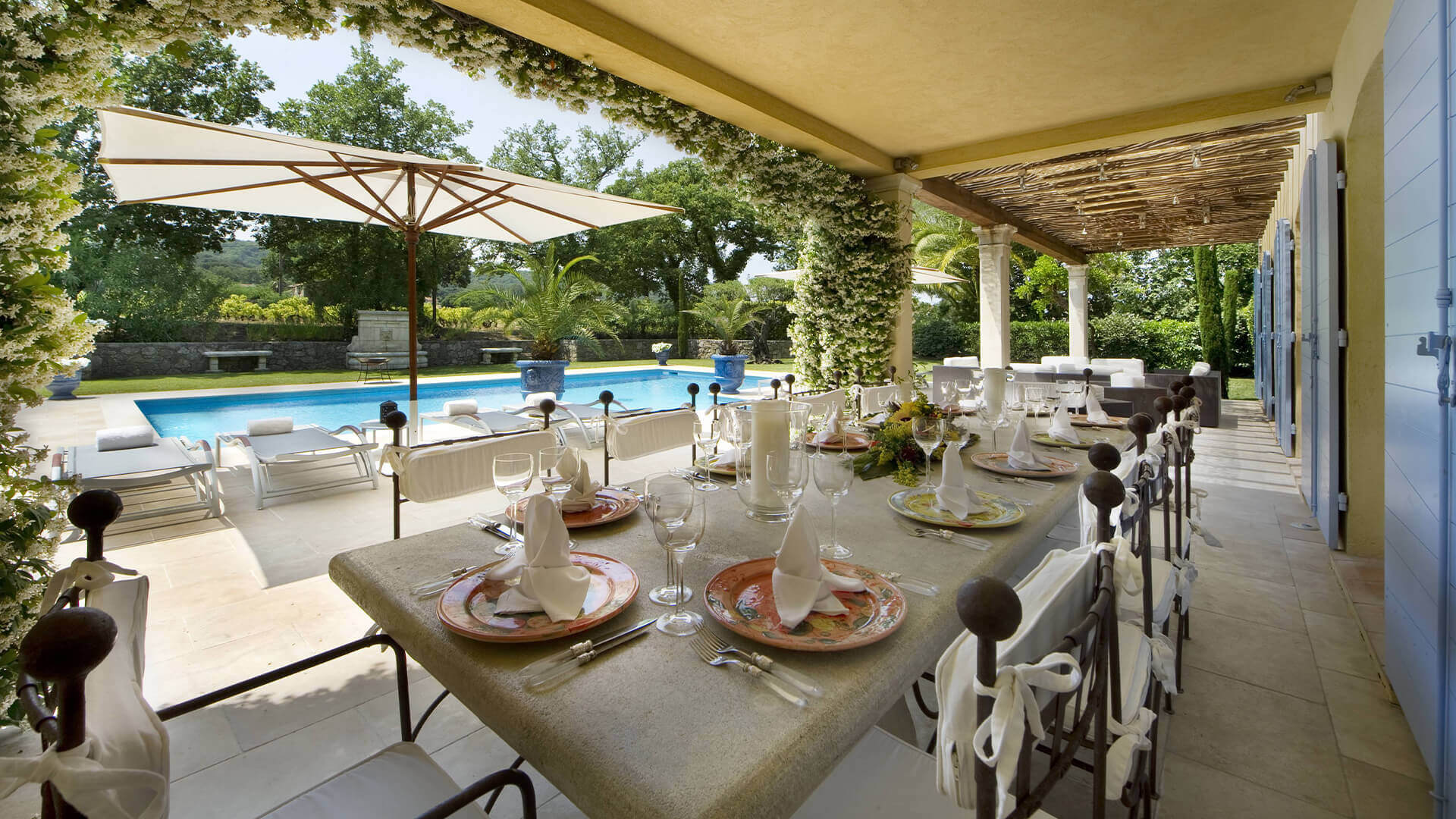 Saint Tropez Villa outside dining area with set table and swimming pool