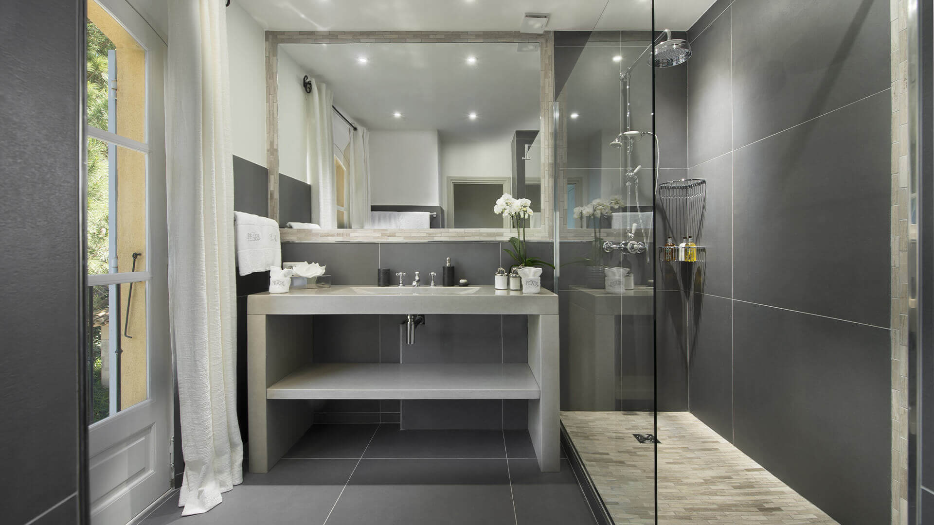 Saint Tropez Villa dark bathroom with large tiles and shower niche