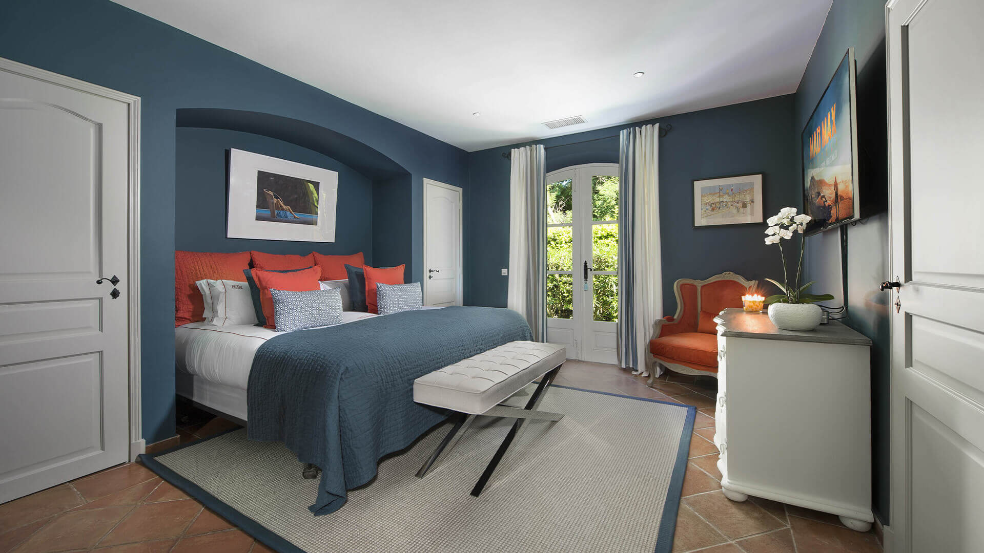 Saint Tropez Villa blue bedroom with red pillows and red chair
